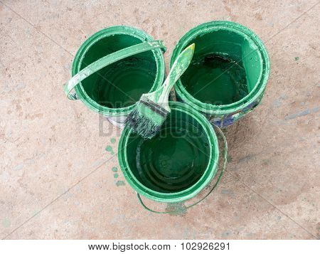 Old paint brush rest on top of green paint Bucket