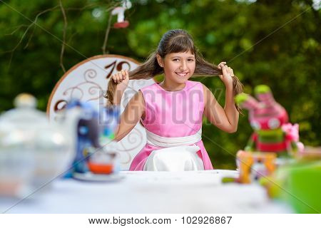 Girl sits at table and pulls her hair. Alice in Wonderland concept