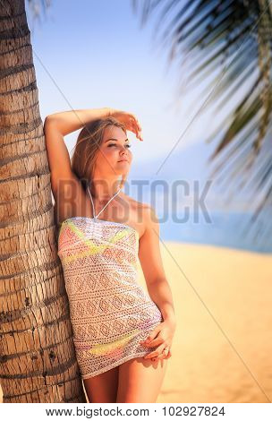 Blonde Girl In Lace Closeup Leans On Palm Trunk On Beach