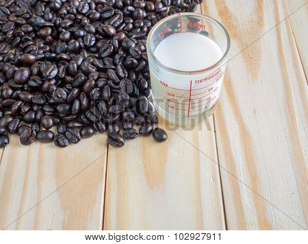 Coffee beans and a measuring cup of fresh milk on wooden board