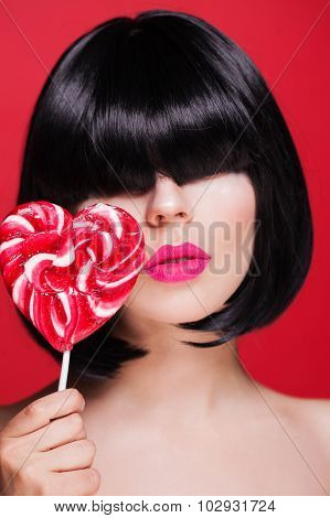Pretty woman posing against red wall and holding big pink lollypop heart.