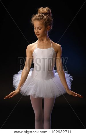 Pretty young ballet dancer posing over black background.
