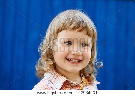 Portrait Of Happy Joyful Beautiful Little Girl Against The Blue Wall