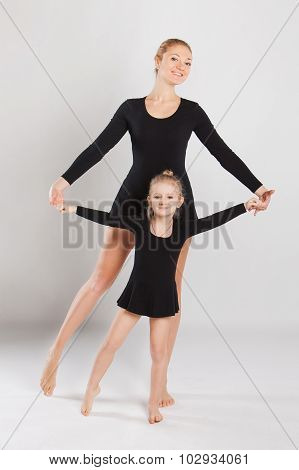 Woman teaching little girl dancing. mother and daughter are gymnastics. on white background