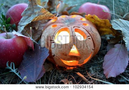 Candlestick pumpkin with a burning candle inside, among autumn fallen leaves and red apples