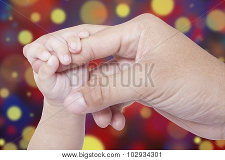 Baby Hand And Father Hand With Bokeh Background