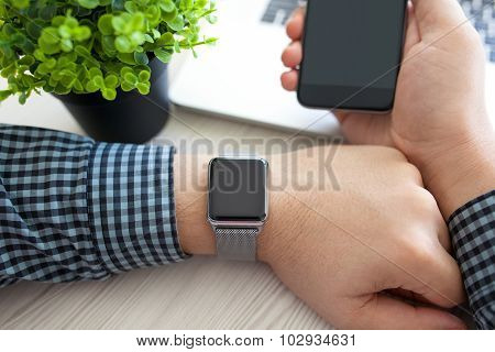 Man Hands With Watch And Phone With A Laptop
