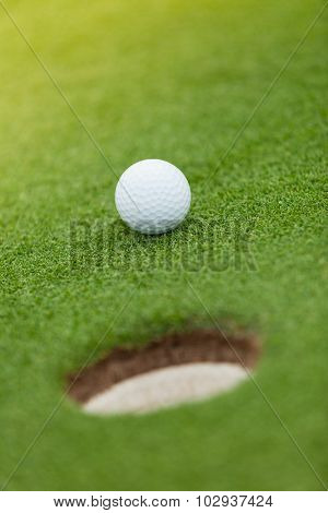 Golf ball on the green lawn with hole