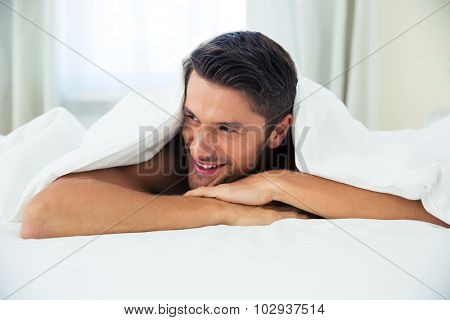 Portrait of a smiling man lying under blanket on the bed at home