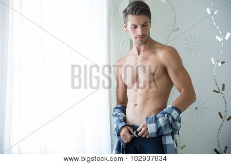 Portrait of a handsome man with perfect body standing at home