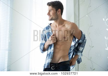 Portrait of a handsome man with muscular body dressing shirt at home