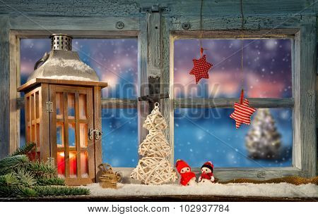 Lantern on window sill in winter mood. Christmas tree on background