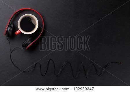 Headphones and coffee cup on black leather desk table. Music concept. Top view with copy space