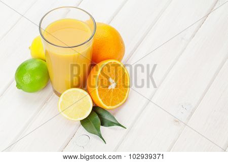 Citrus fruits and glass of juice. Oranges, limes and lemons. Over white wood table background