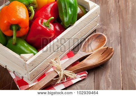 Fresh colorful bell pepper box on wooden table