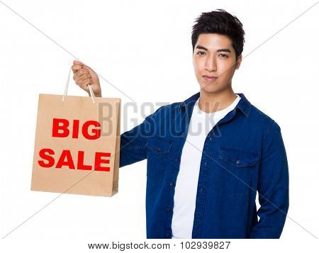 Man hold with shopping bag and showing phrase of big sale