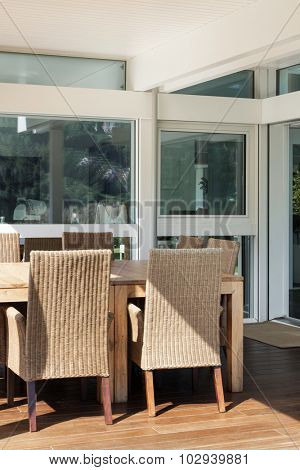 veranda of a modern house, wicker chairs and wooden table
