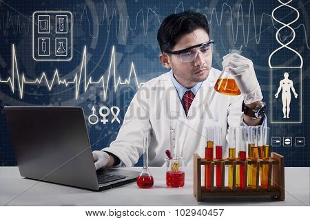 Male Chemist Looking At Chemical Glassware