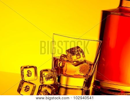Glass Of Whiskey With Ice Cubes Near Bottle On Table With Reflection, Warm Yellow Tint Atmosphere