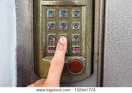 finger presses the button on the intercom