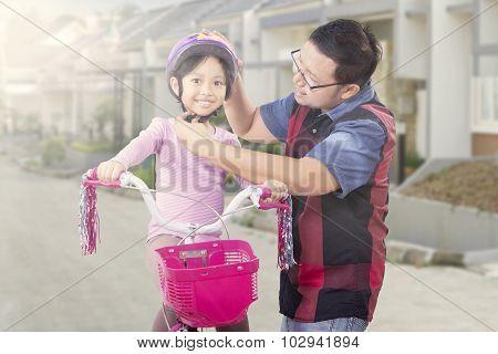 Man Attaching Helmet On The Girl Head