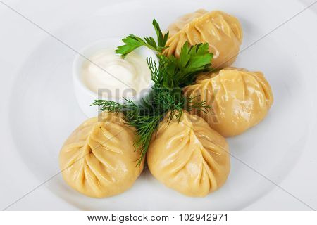 manti parsley with sour cream and dill on a white background plate to the menu
