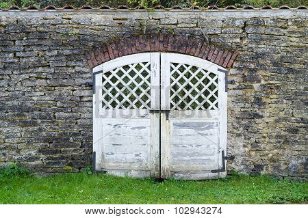 White Weathered Wooden Gate In Old Limestone Wall