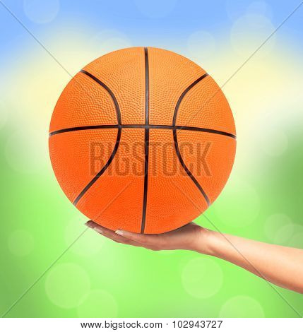 Basketball Ball On Woman Hand Over Bright Nature Background