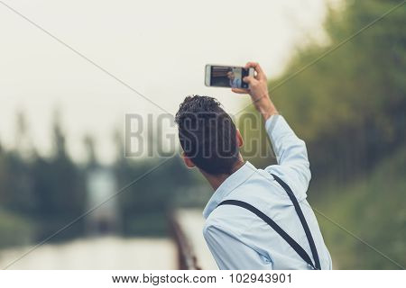 Young Handsome Man Taking A Selfie By A River