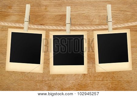 Photo Cards Hanging On Rope Over Wooden Background