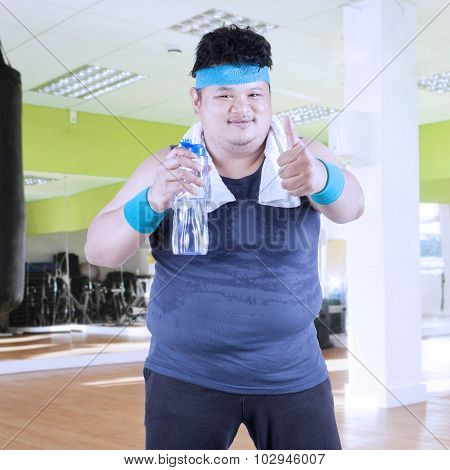 Obese Man Drinks Water At Gym 1