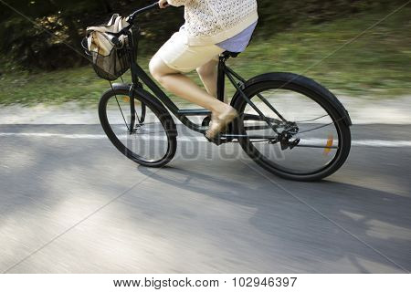 Riding bicycle on the forest road. Close-up of young woman riding bicycle