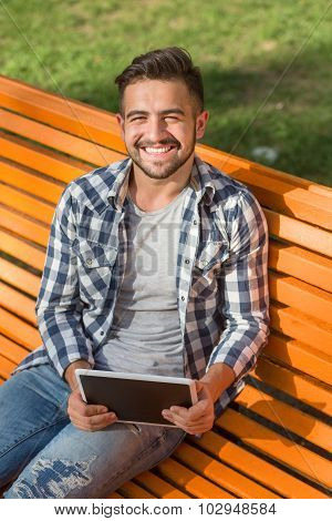 Young man working on tablet PC outdoors
