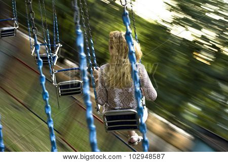 Young beautiful girl rides on a swing suspended on chains
