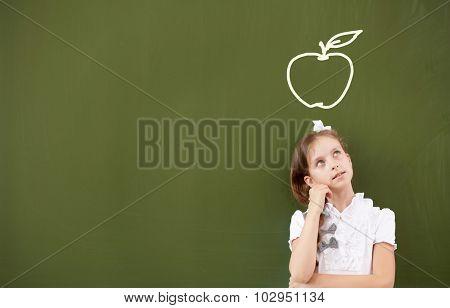 Pretty girl of school age standing at blackboard