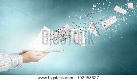 Tablet pc in businessmans hand and papers flying of screen