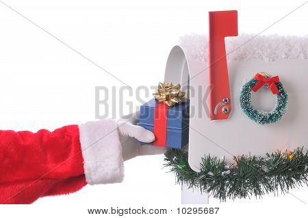 Santa Claus Putting Present In Mailbox