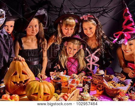 Children on Halloween party  making carved pumpkin