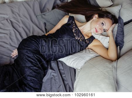 young brunette woman in loft laying on bed smiling seductive close up