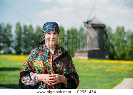 Russian woman in traditional Russian dress and scarf on the back