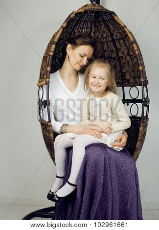 Portrait of mother and daughter at home, happy family in chair