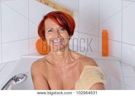 Happy Middle Aged Woman Washing Her Arm With A Face Cloth