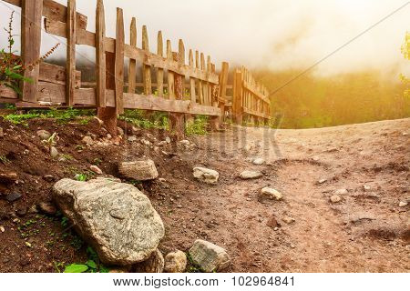 Dirt ground road with rocks and wooden fence in the misty mountains