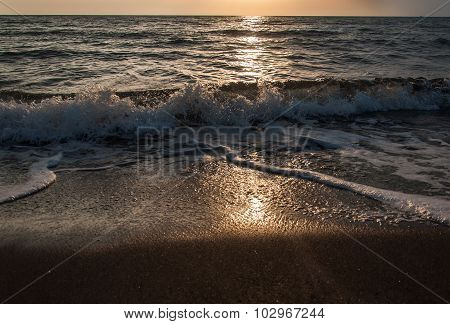 sunset on the beach with black sand.