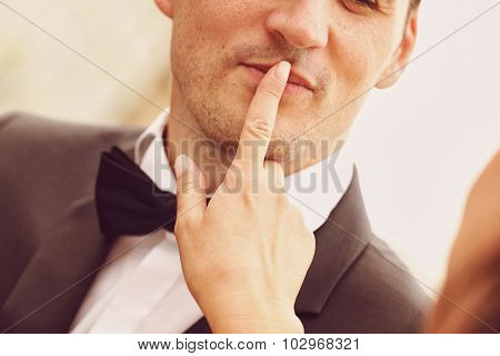Bride making shush sign with groom