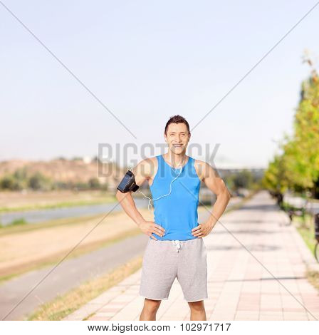 Young athlete listening to music on his cell phone and standing on a sidewalk shot with tilt an shift lens