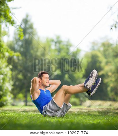 Young athlete doing sit-ups with raised legs in a park on a beautiful summer day shot with tilt and shift lens