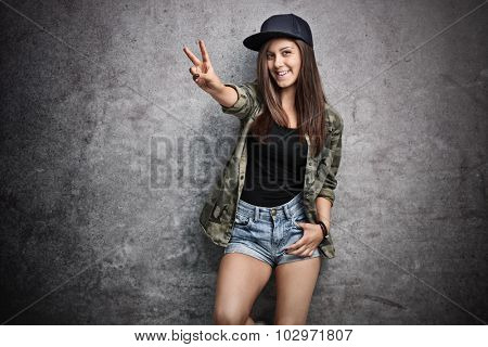 Teenage girl in trendy hip-hop clothes making a peace sign with her hand and posing in front of a rusty gray wall