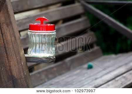Empty jar with plastic cover on a  wooden board