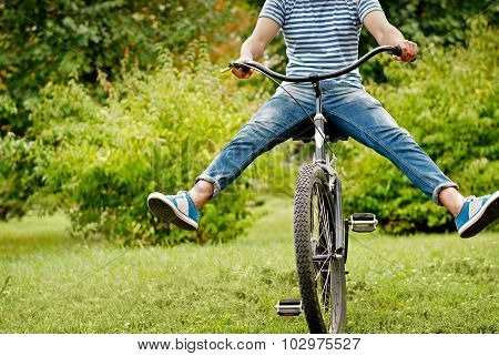 Young Man Riding Bicycle With Her Legs In The Air